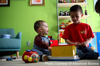 two boys playing with toys, one has a cochlear implant | photo courtesy of Advanced Bionics